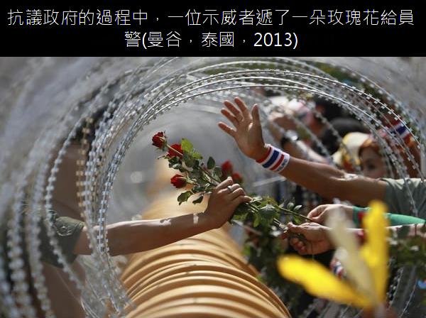 09.抗議政府的過程中,一位示威者遞了一朵玫瑰花給員警.png