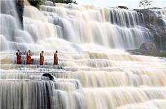 越南達拉,佛教僧侶從磅古瀑布旁走過。