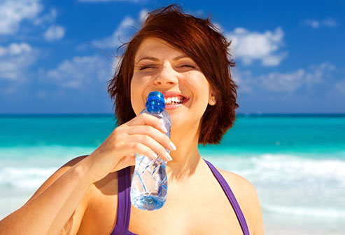 getty_rm_photo_of_woman_guzzling_water_at_beach.jpg