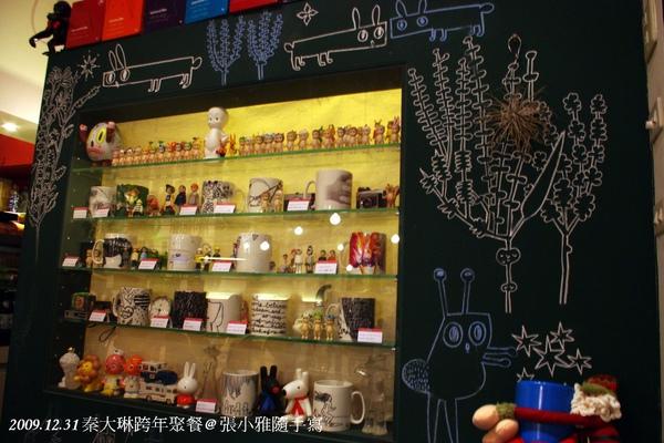 入口處有面放滿杯具和玩具的玻璃牆