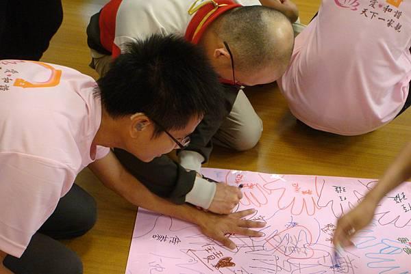 1新進的營隊夥伴,在全方位心靈契約上留下手掌及簽名.JPG