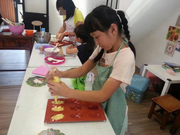 小孩穿上圍裙作蛋糕