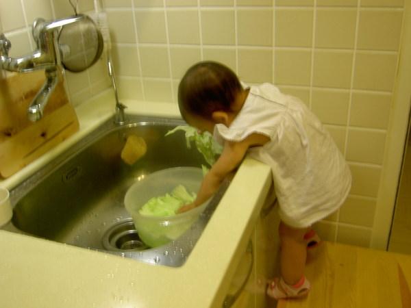 彎下腰來把菜攪一攪,洗乾淨