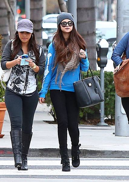 Selena-Gomez-accessorized-her-cheeky-skeleton-sweater-fold-over-leather-boots-fringed-knit-Cooperative-scarf-charcoal-gray-beanie-Dolce-amp-Gabbana-tote-while-shopping-around-LA