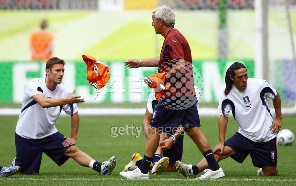 Italian coach Marcello Lippi (C) throws a bib to forward Francesco Totti (L) as midfielder Mauro Cam