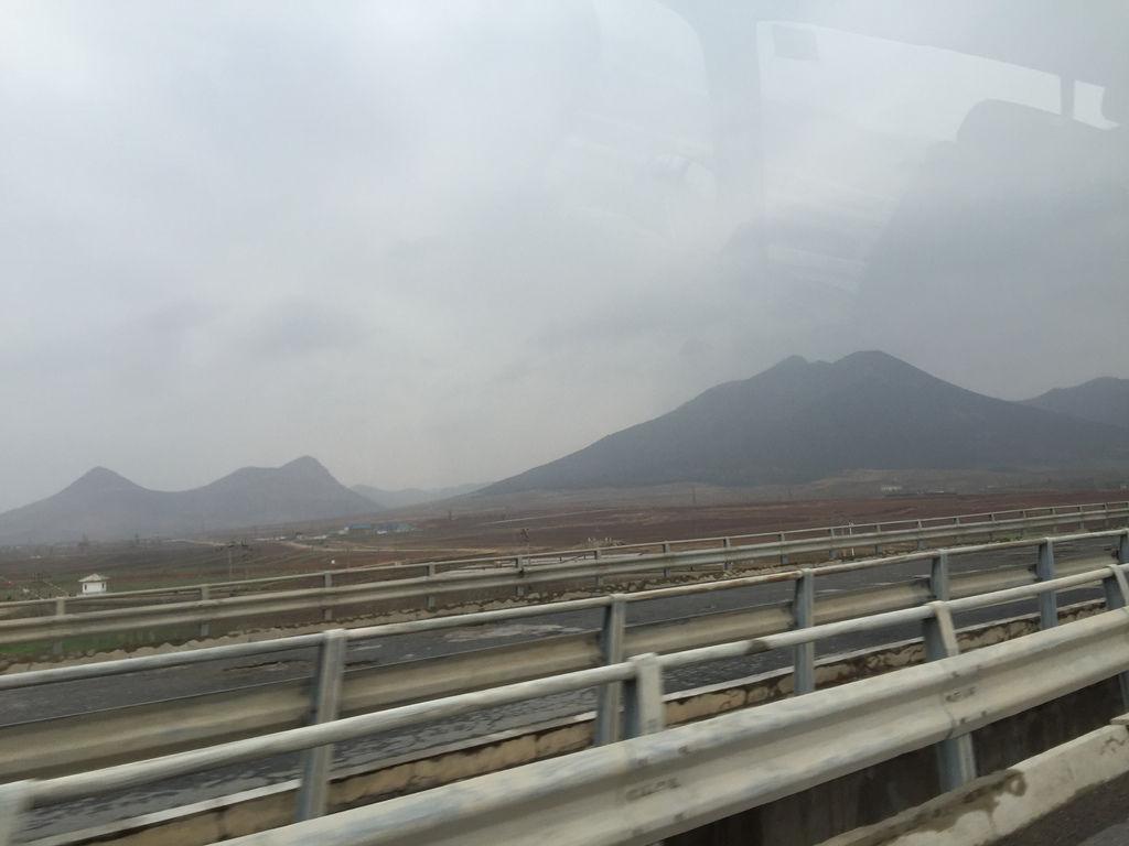 由平壤往開城工業區的路上我們得以一瞥北韓政府不想讓我們看到的真實面向,高速公路的路面年久失修凹凸不平,兩邊無限延伸的貧瘠紅土參雜著零星稀疏的田地.jpg