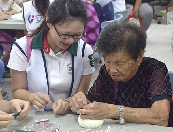 安信志工與長輩一同進行DIY手做活動,過程中也幫助長輩增加手部的運動.jpg