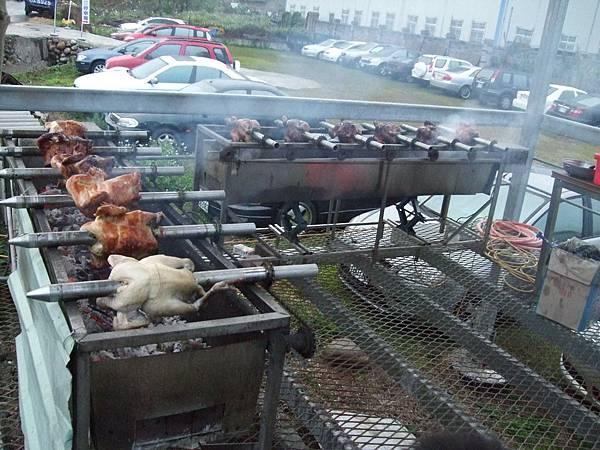 營地在戶外烤鋼管雞,香味四溢。