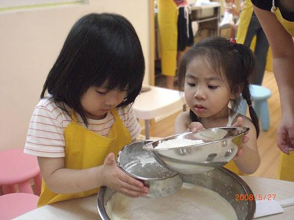 小瞳瞳過篩麵粉,媽媽在旁邊鼓勵她