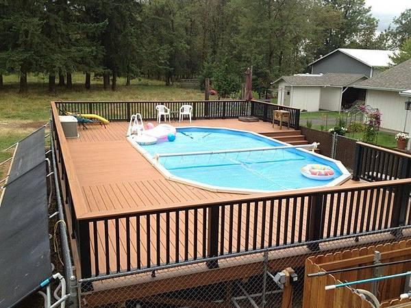 Contemporary-oval-above-ground-pool-with-wooden-deck-and-railing.jpg