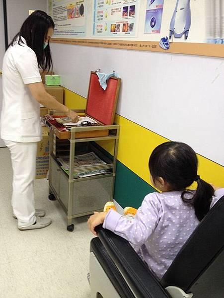 2014-10-22。。等候護士幫妞妞戴眼鏡,做視力檢查