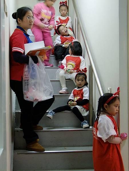 再來是第二首表演。小朋友們換完裝,在樓梯間等待。