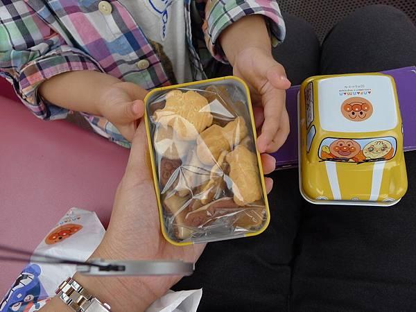 我坐的車廂比較貴可以吃東西,我打開剛剛他挑的鐵盒車子。裡面有餅乾他好開心~