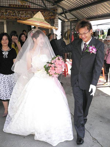 新郎拿著草帽遮住新娘