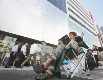 蘋果平板電腦iPad預定廿八日在日本開賣,十九歲的山中竹千代廿六日起就在東京銀座蘋果專賣店外排隊,坐在椅子上看雜誌準備長期抗戰。(路透).jpg