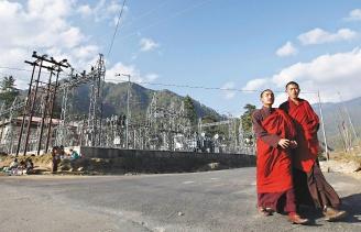 不丹為了要拚經濟,可能不得不犧牲他們引以為傲的國民幸福指數。圖為兩名小和尚經過首都辛布的一座電廠。(路透).jpg