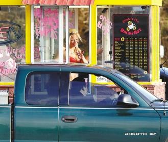 (圖為艾佛瑞特一個咖啡攤穿著清涼的咖啡西施,在收錢後向顧客揮手道別。美聯社).bmp