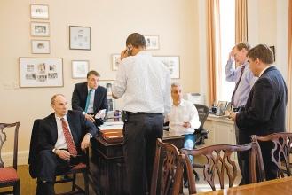 美國眾院廿一日表決健保改革法案當天,歐巴馬總統(背對者)在白宮幕僚長辦公室親自打電話催票。(美聯社).bmp