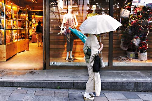 日本經濟長期低迷,政府不斷採取各項刺激方案並維持利率接近零,都無法讓景氣徹底復甦。圖為東京街頭一名穿和服的女子在商店外觀望。(美聯社).jpg