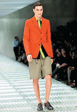 ▲Prada春夏染上制服癖,這件是從義大利郵差穿著衍生出的橘色外套,搭配黃綠條裝飾藍色襯衫及短褲,腳上矮子樂休閒鞋更是小個子男性的福音。(美聯社).jpg