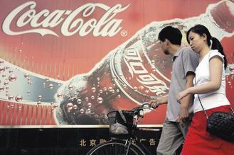 行人走過北京市區一處可口可樂廣告。可口可樂獨霸大陸軟性飲料市場,正在計畫擴大投資,增加設廠,以期更上層樓。歐新社.jpg