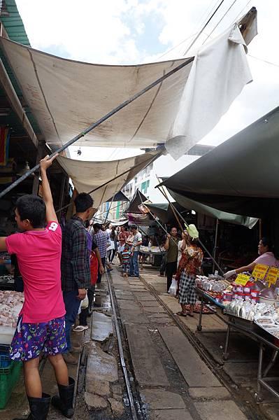 火車駛離,攤販們立即放下遮陽棚和攤子