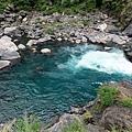 俯瞰白色水浪流入藍綠色潭水