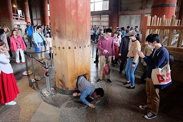 遊客排隊鑽過柱中洞