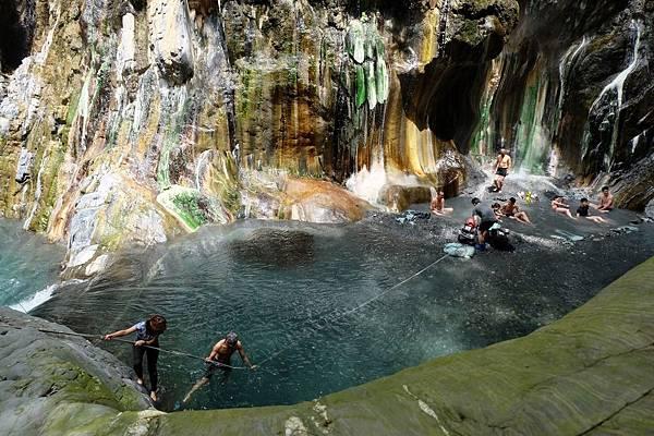 拉繩攀下岩壁游入溪流