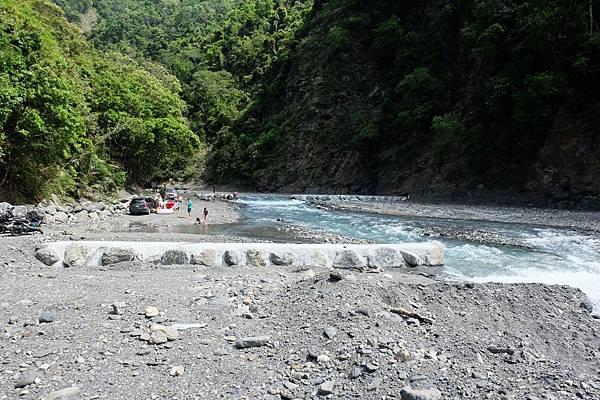 河邊有人在戲水和野餐