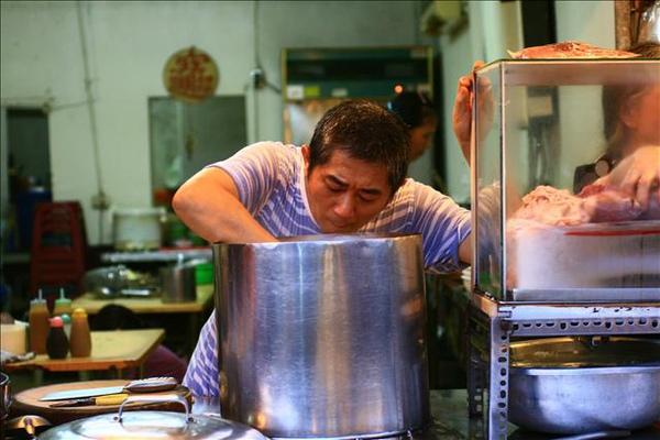 老闆正在把新鮮豬心裝進鍋裡,準備蒸熟