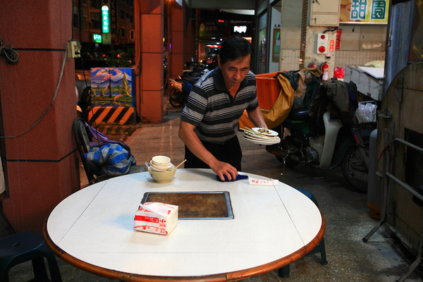 老闆蔡朝裕在整理桌子