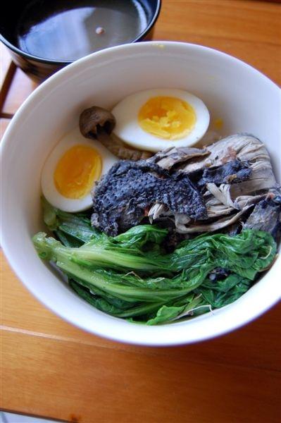這烏骨雞其實是用他之前去喝春酒帶回的菜尾變化而成,搭配白煮蛋及青江菜,配色相當迷人。只是這半剖蛋跟菇菇擺放的方式,怎麼令我有其他聯想咧!