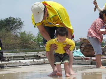 大朋友抱著小朋友赤腳踩在鹽田結晶池體驗腳底按摩的滋味