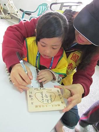 志工媽媽與女兒一起在紀念樹牌上寫下生命經驗中的重要故事,並為自己的樹苗命名