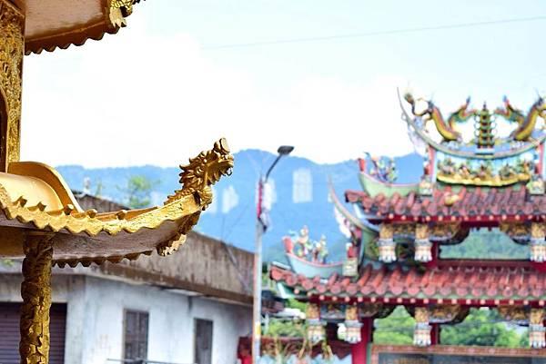 在金色的龍雕後隱約可見遠方山坡上的高樓聚落