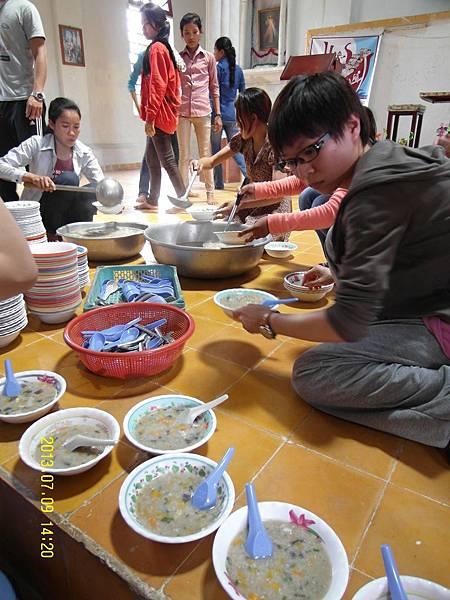 志工正裝著Rice soup給教堂的孩童吃