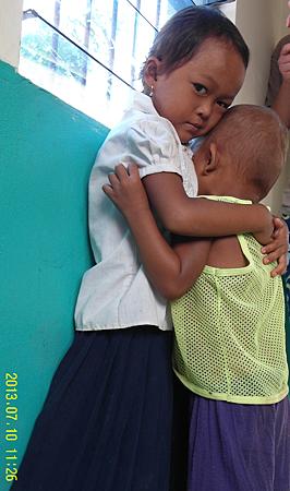 14-0 在孩童身上讓我感動的是,彼此之間情感依賴與照顧,這位小女孩一聽到弟弟哭了,馬上放下手中的碗,跑去抱住並安撫哭泣的弟弟,族群照顧的力量與文化深入每位孩童,使孩童都懂得小孩照顧小孩。_縮圖.png
