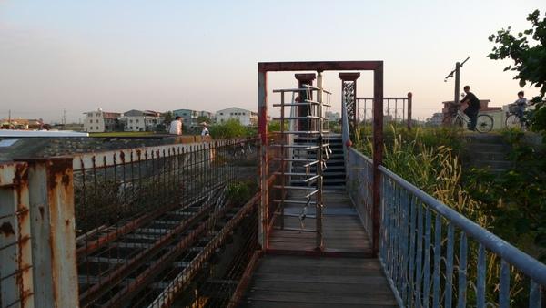 鐵橋的另外一端,旁邊的單車道出入口像是公園裡的旋轉杆一般