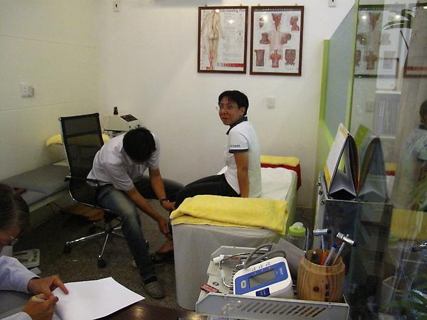 年輕的台灣治療師正在看KK腳踝的痛處