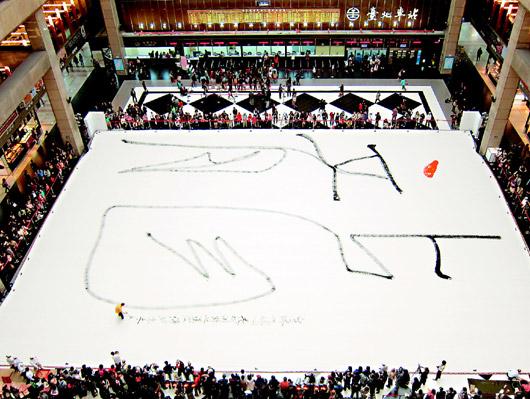 地球禪者、書法家洪啟嵩昨天在台北車站大廳長卅八公尺、寬廿七公尺的棉布上,寫下大大的「龍」字,為台北市漢字文化節揭開序幕。(記者郭安家/攝影)