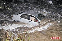 張定維一家四口乘坐的轎車衝入溪中,被暴漲的溪水沖走,女兒落水失蹤。.jpg