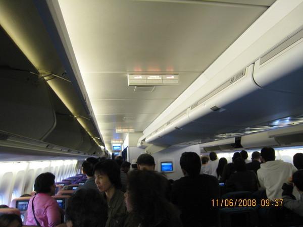 疲憊的旅客排隊準備下機