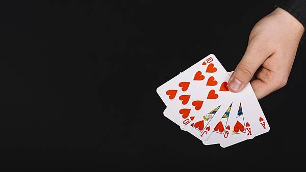 poker-player-s-hand-with-royal-flush-heart-black-background-min.jpg