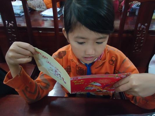 anh 15可愛孩童認真閱讀董事長的信.JPG