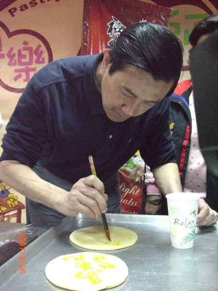 馬英九先生在酥餅上提筆揮毫.JPG