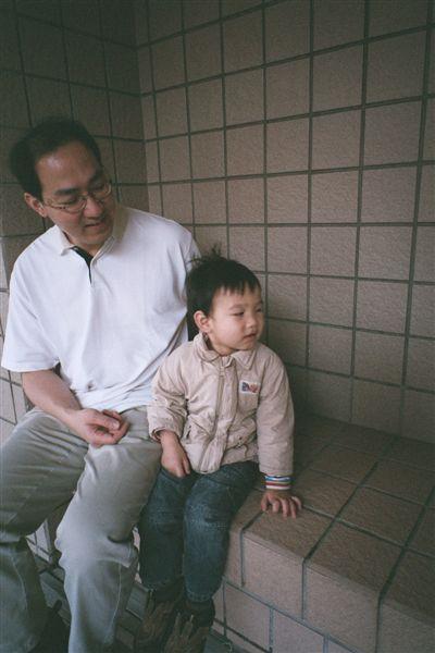 在等捷運的兩父子,兒子在生氣。