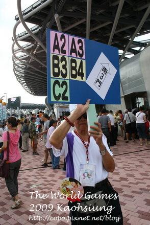 志工拿著指示牌指引入口方向。