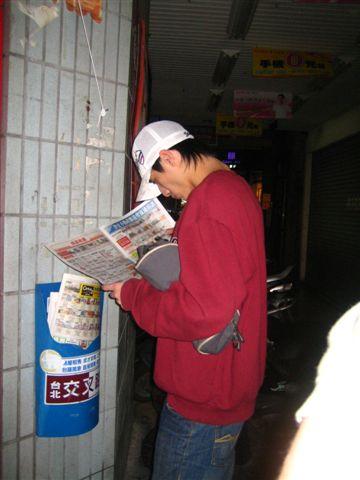 臭弟很無聊的在旁邊看起報紙