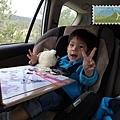 坐在車上抱著熊熊玩磁鐵紙娃娃,不肯下車的Q寶